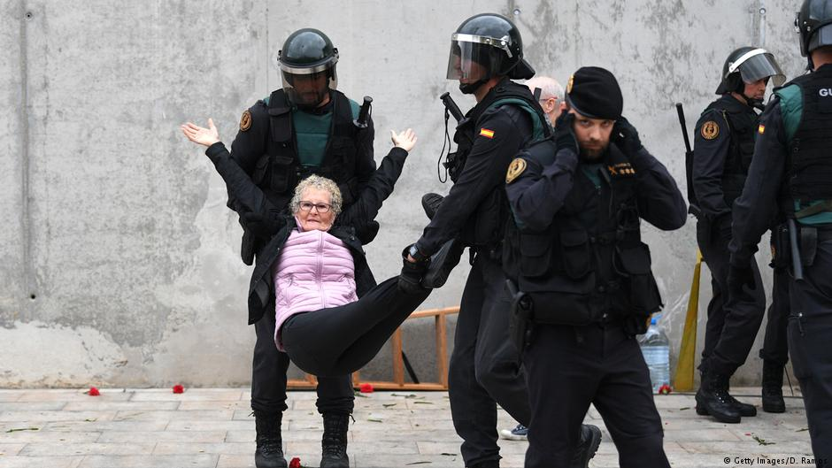 Police remove a woman from a polling station in Sant Julia de Ramis by force